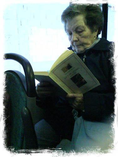 Unha muller lendo un libro de Galaxia no autobús. XAN CARBALLA